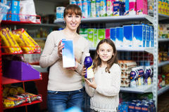 Woman with daughter buying milk Royalty Free Stock Images
