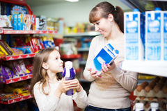 Woman with daughter buying milk Royalty Free Stock Image