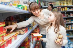 Woman with daughter buying sweet yoghurts stock photo