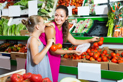 Woman with daughter buying tomatoes Royalty Free Stock Photo