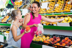 Woman with daughter buying various fruits Stock Image