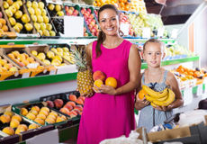 Woman and daughter buying various fruits in marketplace Stock Image