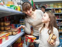 Woman with daughter buying yoghurts Stock Photography