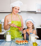 Woman and daughter in cap preparing omelette Stock Photos
