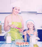 Woman and daughter in cap preparing omelette Stock Image