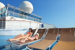 Woman and daughter on chaise longue. Woman and her daughter both wearing swimsuit on chaise longue royalty free stock photography