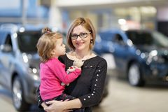 Woman with daughter choose car. In dealership Stock Image