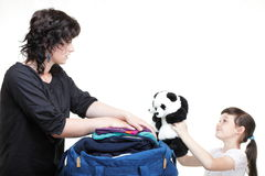 Woman and daughter crammed clothes into one bag Stock Photo