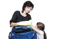 Woman and daughter crammed clothes into one bag Stock Photos