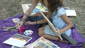 Woman with daughter drawing by watercolor paints at the park stock video