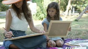 Woman with daughter drawing by watercolor paints at the park stock video footage