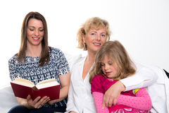 Woman with daughter and grandchild together reading in book Royalty Free Stock Photo