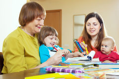 Woman  with daughter and grandchildren sketching  on paper Royalty Free Stock Photo