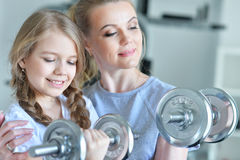 Woman with daughter in a gym. Portrait of a young women with her teenage daughter in a gym with dumbbells Stock Image