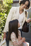 Woman With Daughter Holding Handbags In Frontyard Stock Photography