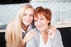 Woman with daughter on kitchen Stock Photography