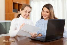 Woman and daughter with laptop. Smiling mother and daughter with financial documents and laptop at table in home interior stock image