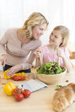 Woman And Daughter Looking At Each While Preparing Salad Royalty Free Stock Photo
