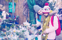 Woman with daughter looking at floral decoration at Cristmas fai. Happy russian women with daughter looking at floral decoration at Cristmas fair Royalty Free Stock Image
