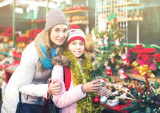 Woman with daughter looking at floral decoration at Cristmas fai. Happy spanish women with daughter looking at floral decoration at Cristmas fair Royalty Free Stock Images