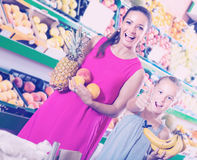 Woman with daughter looking satisfied in fruit store Royalty Free Stock Image