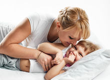 Woman and daughter lying in bed smiling Stock Photography