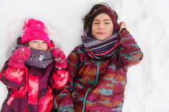 Woman , daughter lying on snow Royalty Free Stock Photo