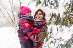 Woman , daughter near evergreen trees Royalty Free Stock Images