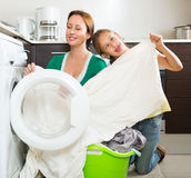 Woman with daughter near washing machine Stock Photos