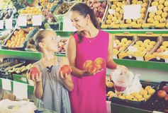 Woman with daughter picking peaches Stock Images