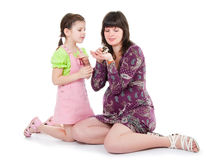 Woman and a daughter play with a hamster Stock Photos