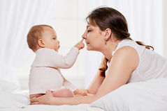 Woman and daughter playing in bed Royalty Free Stock Images