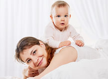 Woman and daughter playing in bed Royalty Free Stock Photography