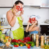 Woman and daughter playing with vegetables. Happy women and her daughter playing with vegetables and cooking healthy dinner Stock Image