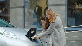 Woman with daughter plugging in her electric car to charge on the parking lot