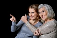 Woman with daughter posing. Portrait of Senior women with daughter posing on dark background Stock Images