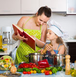 Woman and daughter preparing food consulting the cookbook Royalty Free Stock Images