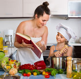 Woman and daughter preparing food consulting the cookbook Royalty Free Stock Photos