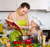 Woman and daughter preparing food consulting the cookbook Royalty Free Stock Photo