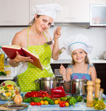 Woman and daughter preparing food consulting the cookbook. Smiling american women and daughter preparing food consulting the cookbook Royalty Free Stock Photo