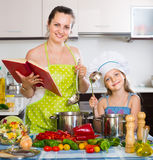 Woman and daughter preparing food consulting the cookbook Stock Photo