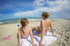 Woman and daughter relaxing on a beautiful beach together on vacation Stock Photos