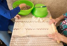 Woman and daughter rolls out dough in the kitchen.  Royalty Free Stock Photography