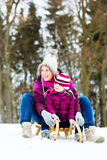 Woman and daughter on sled in winter Stock Photos