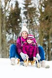 Woman and daughter on sled in winter royalty free stock photography