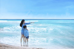 Woman and daughter standing at coast Stock Photos