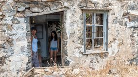 Woman and daughter standing in ruins of abandoned house royalty free stock photography