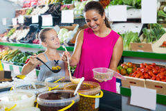 Woman with daughter taking pickled olives from bucket Stock Photos