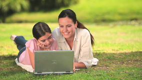 Woman and daughter using a laptop outdoors Royalty Free Stock Photo