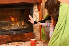 Woman with daughter warming hand at fireplace Stock Images